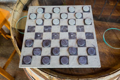 Checkers Game on Wine Barrel Table. Wine barrel table with glass top plays host to this game of checkers stock images