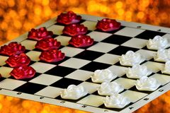 Checkers of roses on a checkered Board, the competition on a festive sparkling background. Checkers is a popular ancient Board. Logic antagonistic game, on a stock photography