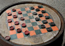 Checkers on a Wood Barrel. Worn game of Checkers painted on a wooden cracker barrel royalty free stock photo