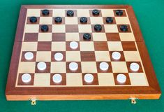 Checkers on wooden board on green table. Checkers on wooden checkered board on green baize table royalty free stock photography
