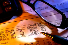 Checking Account Statement with Glasses and Pen. Pen on a bank checking account financial statement with glasses and calculator for budgeting and reconciliation