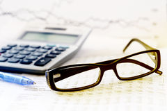 Checking accounts with a calculator. And glasses royalty free stock photo