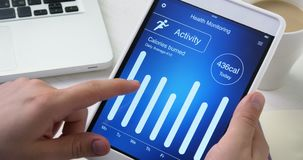 Checking activity monitoring on health app on the digital tablet stock video footage