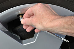 Checking the Air Pressure of a Tire. With a Tire-Pressure Gauge Royalty Free Stock Photo