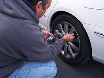 Checking air pressure in tire stock image