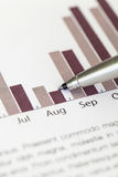 Checking the annual sales chart with ballpoint pen stock photography