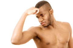 Checking arm muscles. Bodybuilding man checking arm muscles, with unhappy expression stock photos