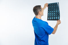 Turned back medical worker examining mri scan image. Checking attentively. Waist up shot of a male practitioner wearing a navy blue attire lifting an x ray scan stock images