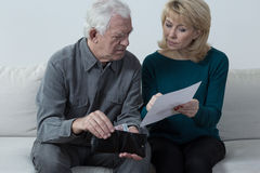Checking the balance. Older troubled married couple checking the balance Royalty Free Stock Image