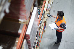 Checking barcodes. Worker with scanner making review of goods in warehouse Stock Images