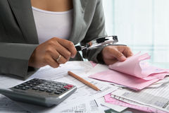 Checking bills with magnifying glass. Businesswoman checking bills using magnifying glass in the office Stock Photography