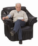Checking  the blood pressure. Senior man checking his own blood pressure while sitting in a comfortable armchair Royalty Free Stock Photos