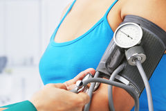 Checking blood pressure of female patient stock image