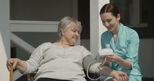 Checking Blood Pressure to Elderly Woman Nurse is Smiling and Caring for Old People Outdoors on Sunny Day at the Nursing Home shot stock video