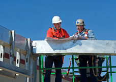 Checking the Blueprints. Construction superintendent checking the blueprints with a worker Royalty Free Stock Image