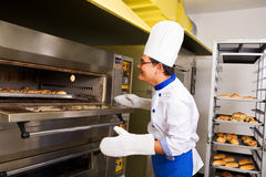 Checking the bread inside oven Royalty Free Stock Photography