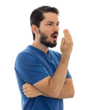 Checking the breath, man in casual clothes. Isolated on white ba. Male checking his breath with the hand. Bad breath. Halitosis concept royalty free stock photos