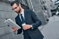 Checking business news. Good looking young man in full suit read. Ing a newspaper while sitting outdoors royalty free stock photo