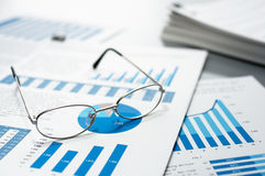 Checking business reports. Glasses and pile of documents. Stock Image