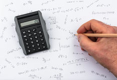Checking the calculations on a pocket calculator. Person doing calculations on paper and calculator Royalty Free Stock Photo