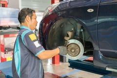Checking car brake system. Bangkok, Thailand - January 16, 2016 : Unidentified serviceman checking brake system in a car at garage stock images