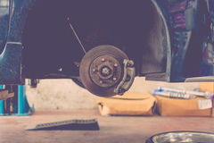 Checking car brake system. Checking car brake and suspension system in a car for repair at garage , process in vintage style stock photography