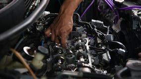 Checking a car engine for repair at car garage. Bangkok, Thailand - April 29, 2017 : Unidentified car mechanic or serviceman checking a car engine and valve for stock footage