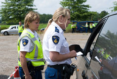 Checking car papers. HAAKSBERGEN, NETHERLANDS - JUNE 09: Two policewomen are checking the papers of a car driver during a massive car control, june 09, 2011 in Stock Photo