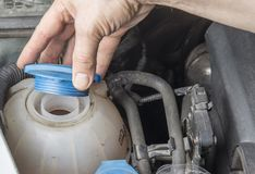 Checking car radiator coolant level and add up liqiud.  Stock Photography