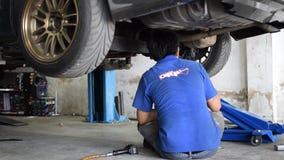 Checking car suspension. Bangkok, Thailand - January 22, 2016 : Unidentified serviceman checking suspension in a car at garage stock video
