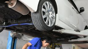 Checking car suspension. Bangkok, Thailand - October 1, 2016 : Unidentified serviceman checking suspension in a car at garage stock video