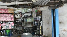 Checking car suspension. Bangkok, Thailand - October 1, 2016 : Unidentified serviceman checking suspension in a car at garage stock video footage