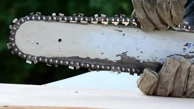 Checking the chain saw bar for tightness stock video