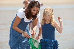 Checking the content of the net. Mother and daughter by the seaside fishing with shrimpnet Royalty Free Stock Image