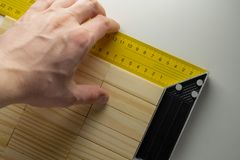 Checking the corner of the table, hand with corner ruler and wooden blocks table. stock photo