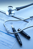 Checking the cost of health care. With stethoscope and pen in foreground Royalty Free Stock Image