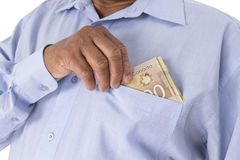 Checking or counting Canadian dollars in hand from pocket. Holding and keeping Canadian dollar banknotes to pocket in white background Stock Images