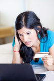 Checking credit card balance. Young woman checking credit card balance and looks worried Royalty Free Stock Image