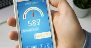 Checking credit score on smartphone using application. The result is AVERAGE stock video footage