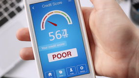 Checking credit score on smartphone using application. The result is POOR stock footage