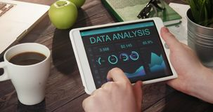 Checking data analysis graphs and charts using digital tablet. At the desk stock footage