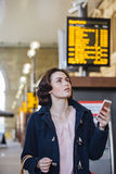 Checking The Departure Board. Young businesswoman is using her smart phone to check for her train time on the departure board Stock Photography