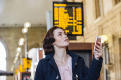 Checking The Departure Board. Young businesswoman is using her smart phone to check for her train time on the departure board Royalty Free Stock Images
