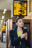 Checking The Departure Board. Young businesswoman is using her smart phone to check for her train time on the departure board Royalty Free Stock Photo