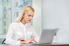 Checking e-mail. Successful business woman sitting at the table Stock Image