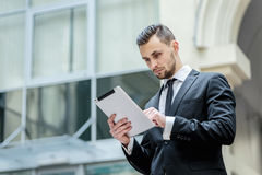Checking e-mail. Young man in formal wear holding a tablet in hi Stock Images