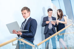 Checking email . Young and successful businessman standing on th. E stairs holding a laptop and smiling and looking into the camera in the meantime there are two Stock Photos