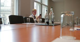 Checking Emails Before the Meeting. Surface level view of a young businessman waiting in a conference room for people to arrive. While waiting he is using his stock video
