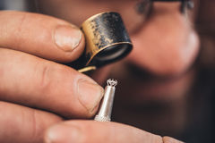 Checking every facet of the diamond. Closeup of a jeweler using a loupe to examine a diamond he is working with while sitting at a bench in his workshop royalty free stock image