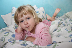 Checking the fever of a sick little girl. A girl is laying in bed, having her temperature checked with an oral fever thermometer, looking quite perky Royalty Free Stock Photography